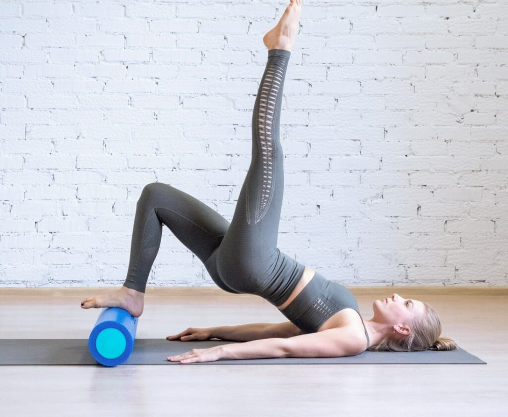 A woman lying on the floor with one leg raised in the air and the other placed on a yoga roll