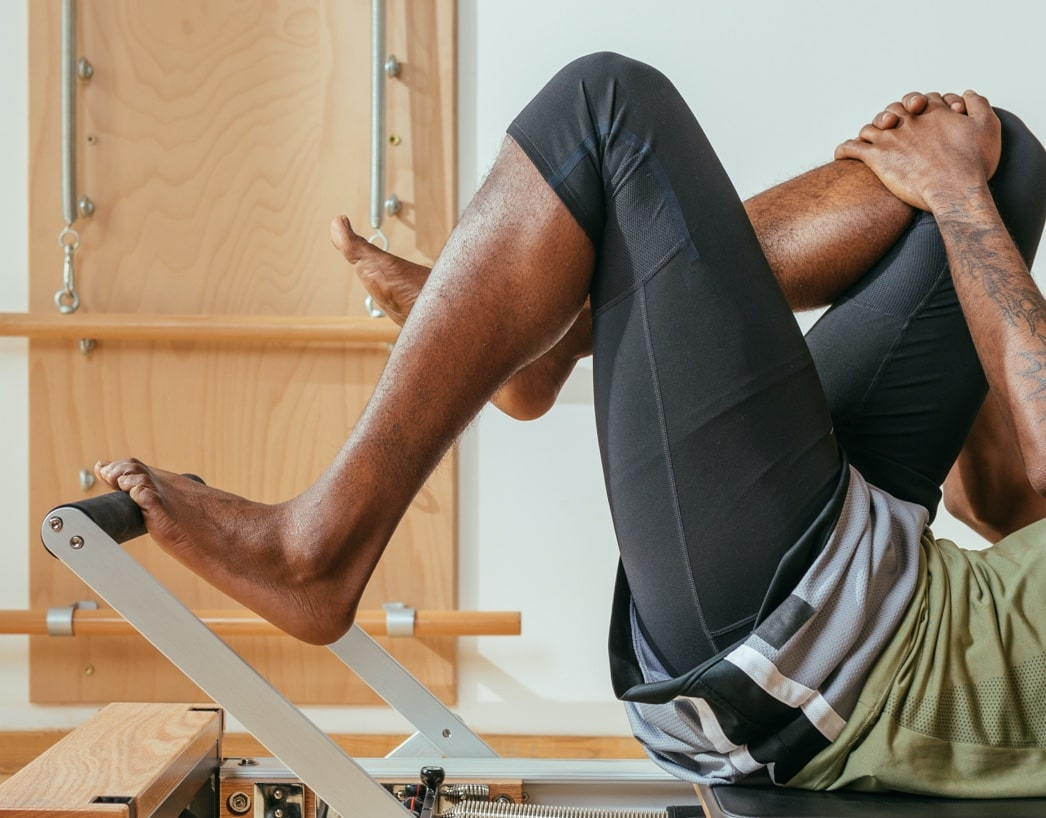 A person lying on an adjustable table and stretching their legs