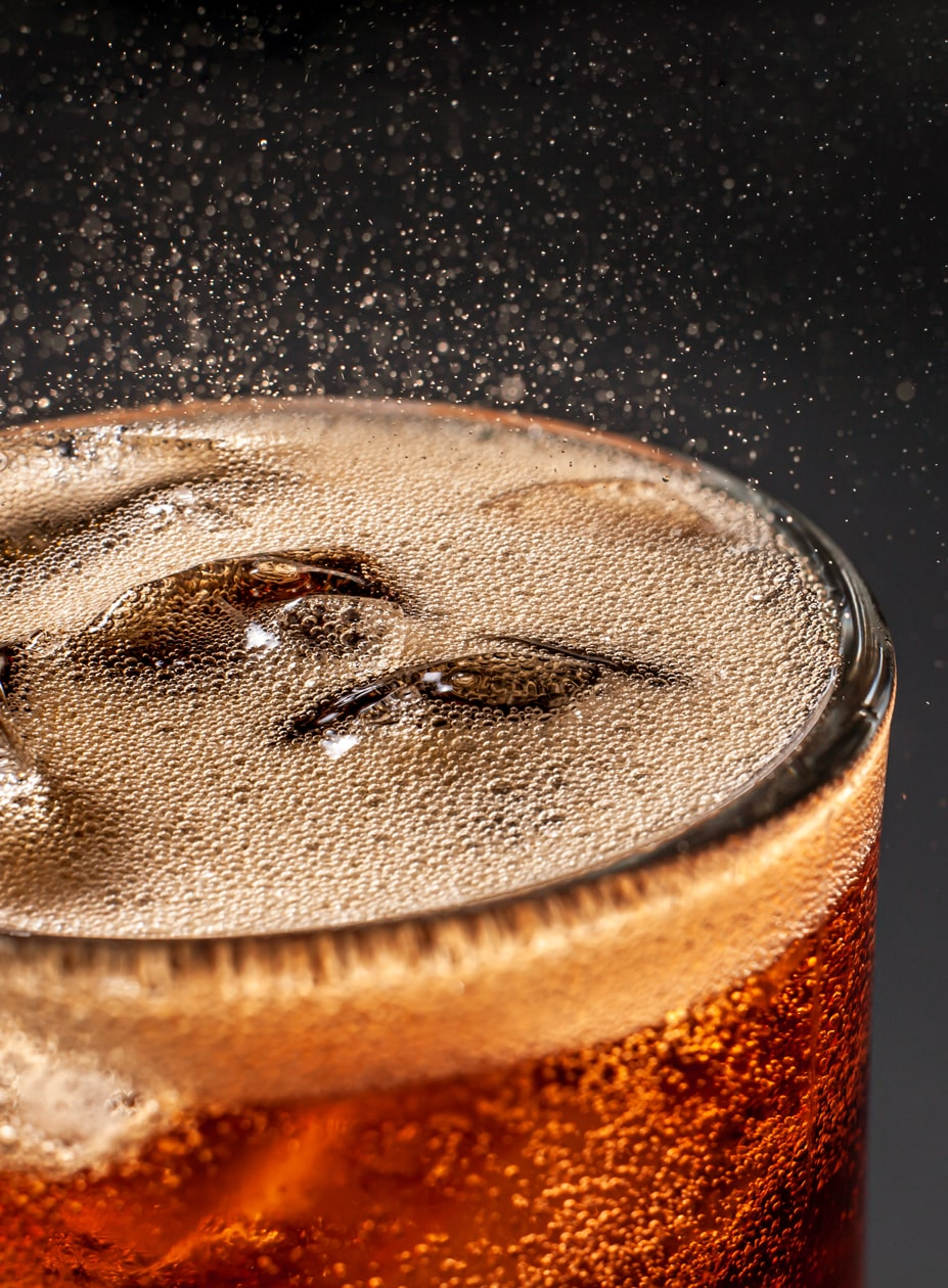 A fizzing glass of soda with ice in it
