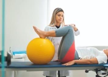 A chirospot expert helping a patient stretch her legs on a medicine ball