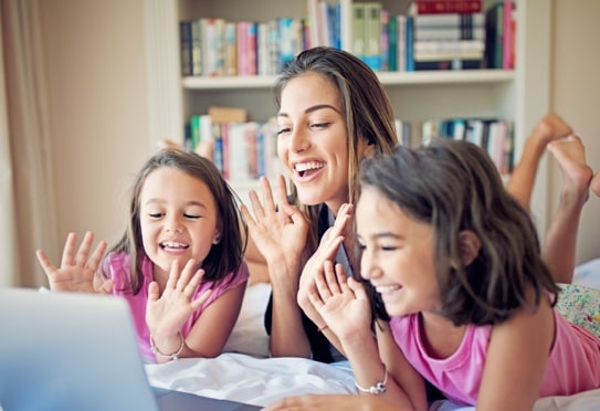 A mother and her two daughters lying on a bed while attending a video call