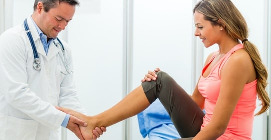 A medical professional examining the foot of a patient for issues.