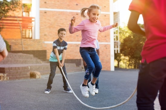A girl playing jump rope while two other children hold the ends of the rope